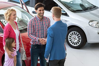 photo of family buying car at automobile dealership